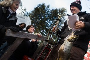 Kasey Johnson of Durham is all smiles as he walks away with a $1,000 check, a trophy and the wining fish at the 13th annual Horne Pond Ice Fishing Derby in Limington on Saturday. It was a 3.810 pound, 20.750 inch brown trout. (Photo by Troy R. Bennett)