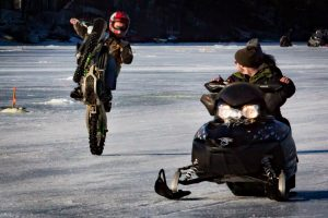 A daredevil on a dirt bike wheelies past a snowmobile at the Horne Pond Ice Fishing Derby on Saturday in Limington. (Photo by Troy R. Bennett)